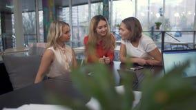 Três colegas de trabalho riem e sorriem discutindo seus casos durante a ruptura Colegas que sentam-se no gracejo da tabela da sal video estoque