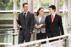 Três colegas do negócio que conversam o passeio imagem de stock