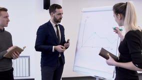 Três colegas que discutem a situação do mercado perto da placa branca na sala do coference video estoque