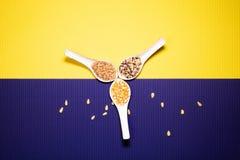 Três colheres com amêndoa e milho do arroz no fundo amarelo e roxo fotos de stock royalty free