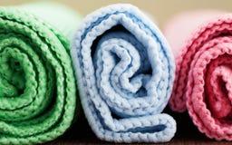 Três coloriram ascendente próximo dos rolos de toalhas de banho Fotos de Stock Royalty Free