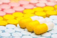 Três comprimidos amarelos no fundo de comprimidos médicos coloridos Imagem de Stock