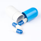 Três comprimidos pequenos estão saindo da cápsula azul e branca grande Foto de Stock