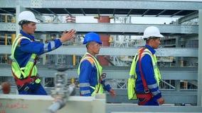 Três coordenadores no capacete de segurança estão movendo-se através de uma fábrica da indústria pesada vídeos de arquivo