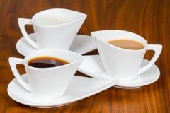 Três copos de café na tabela de madeira marrom Imagens de Stock Royalty Free