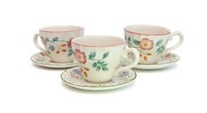Três copos de chá com os saucers isolados imagens de stock