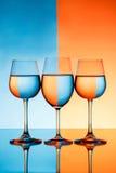 Três copos de vinho com água sobre o fundo azul e alaranjado Fotografia de Stock