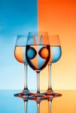 Três copos de vinho com água sobre o fundo azul e alaranjado Foto de Stock