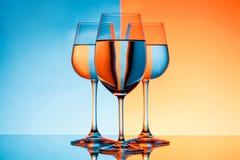 Três copos de vinho com água sobre o fundo azul e alaranjado Foto de Stock Royalty Free