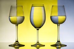 Três copos de vinho com água sobre o fundo cinzento e amarelo Foto de Stock Royalty Free
