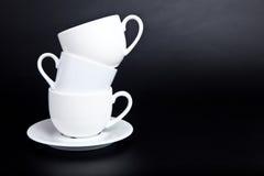Três copos do branco em um preto Fotografia de Stock