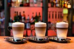 Três copos do latte Fotos de Stock