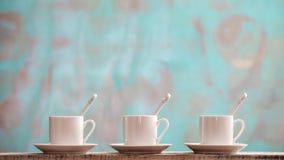 Três copos pequenos da porcelana com colheres e pires contra um fundo verde rústico com espaço da cópia Foto de Stock