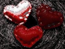 Três corações abstratos em um fundo escurecido Fotografia de Stock
