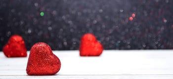 Três corações brilhantes vermelhos com um fundo borrado Fotos de Stock