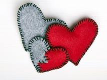 Três corações de feltro em um fundo de madeira branco Imagem de Stock Royalty Free