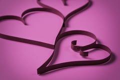 Três corações de papel no papel roxo Fotografia de Stock