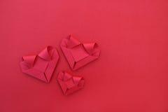 três corações de papel vermelhos de dobramento no vermelho para o teste padrão e o fundo Imagem de Stock