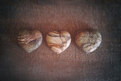 Três corações de pedra na madeira Fotografia de Stock