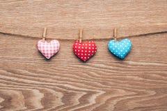 Três corações do amor que penduram no fundo de madeira da textura Fotos de Stock