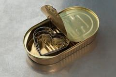 Três corações do metal em uma lata imagem de stock
