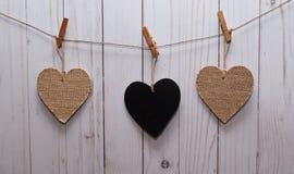 Três corações penduraram em uma linha na frente de uma cerca de madeira Foto de Stock