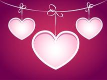 Três corações que penduram em uma corda. Imagem de Stock