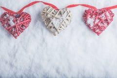 Três corações românticos bonitos do vintage estão pendurando em uma faixa vermelha em um fundo branco da neve Amor e conceito do  Imagens de Stock
