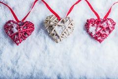 Três corações românticos bonitos do vintage estão pendurando em uma faixa vermelha em um fundo branco da neve Amor e conceito do  Fotos de Stock