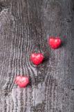 Três corações vermelhos brilhantes no fundo de madeira velho Foto de Stock