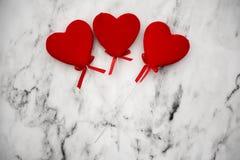 Três corações vermelhos em um fundo de mármore Imagem de Stock Royalty Free