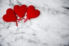 Três corações vermelhos em um fundo de madeira Fotos de Stock