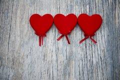 Três corações vermelhos em um fundo de madeira Imagem de Stock Royalty Free