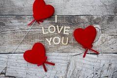 Três corações vermelhos em um fundo de madeira Imagens de Stock Royalty Free