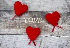 Três corações vermelhos em um fundo de madeira Imagens de Stock