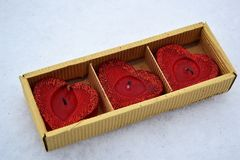 Três corações vermelhos em uma caixa do cortonal - velas na neve branca fotografia de stock royalty free