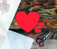 Três corações vermelhos feitos do papel e das tesouras no fundo de madeira escuro velho do grunge Fotografia de Stock Royalty Free