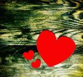 Três corações vermelhos feitos do papel no fundo de madeira escuro velho do grunge Imagem de Stock