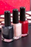 Três cores diferentes do verniz para as unhas e um fundo compor - vermelho, ponto morto e preto Fotos de Stock