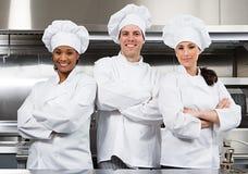 Três cozinheiros chefe imagens de stock
