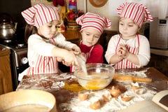 Três cozinheiros chefe pequenos na cozinha Fotos de Stock Royalty Free