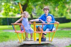 Três crianças adoráveis em um balanço fotografia de stock