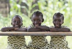 Três crianças africanas que sentam fora o sorriso e o riso imagens de stock royalty free
