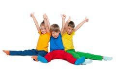 Três crianças alegres mantêm seus polegares Fotografia de Stock Royalty Free