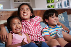 Três crianças asiáticas que sentam-se na tevê de Sofa Watching junto Fotos de Stock Royalty Free