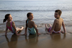 Três crianças bonitos do preteen que sentam-se na água na praia imagem de stock