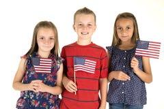 Três crianças bonitos que mantêm bandeiras americanas felizes imagem de stock royalty free