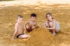 Três crianças Caucasoid felizes nos maiôs constroem uma torre da areia amarela na praia imagem de stock royalty free