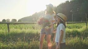 Três crianças das meninas com o ramalhete do dedo da mostra de flores na estrada, nas emoções alegria e na felicidade, esperam e  video estoque