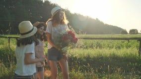 Três crianças das meninas com o ramalhete do dedo da mostra de flores na estrada, nas emoções alegria e na felicidade, esperam e  filme
